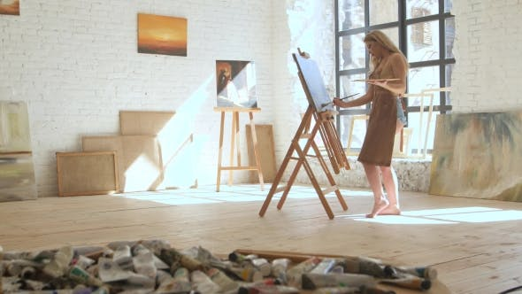 Thumbnail for Woman Artist Paints on Canvas on Easel and Holds Palette in Art Workshop