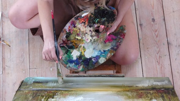 Thumbnail for Girl Artist Paints Picture Sitting on the Floor