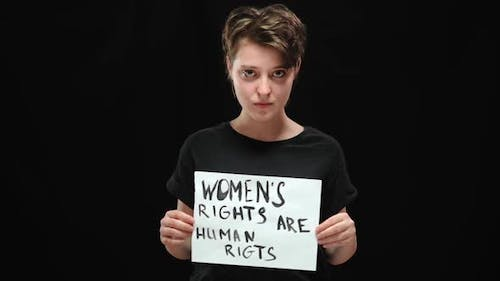 Portrait of Confident Beautiful Brunette Woman Posing with Placard Womens Rights are Human Rights