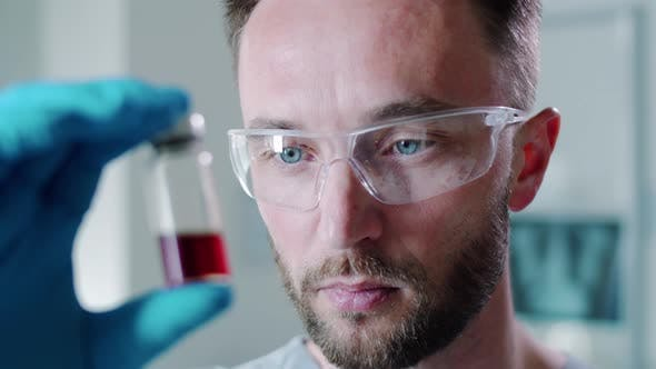 Thumbnail for Male Scientist in Protective Glasses and Gloves Examining Vaccine