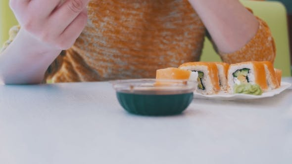 Thumbnail for Woman with Chopsticks Eating Sushi From a Plate in a Japanese Restaurant