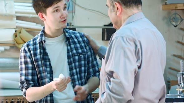 Thumbnail for Senior Worker Laying a Bandage on the Wound on the Finger of Young Trainee in Frame Workshop