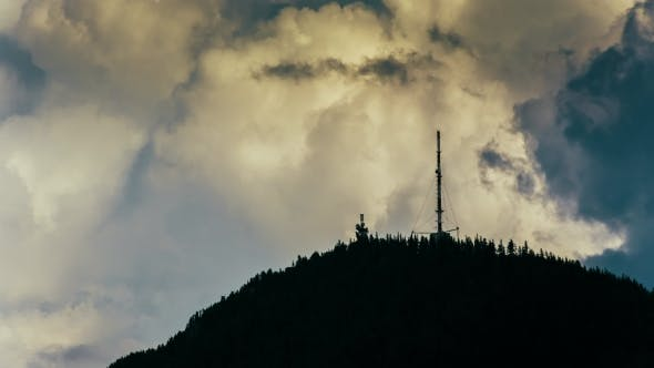 Thumbnail for Radio Tower on Mountain Peak with Hard Clouds Background