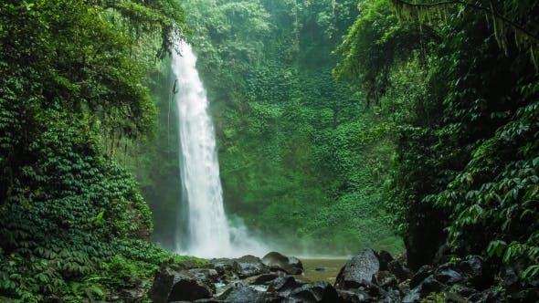Thumbnail for Erstaunlich Nungnung Wasserfall, Fallendes Wasser trifft Wasseroberfläche, einige riesige Felsen sichtbar vor