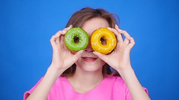 Young Woman Taking Colorful Donuts