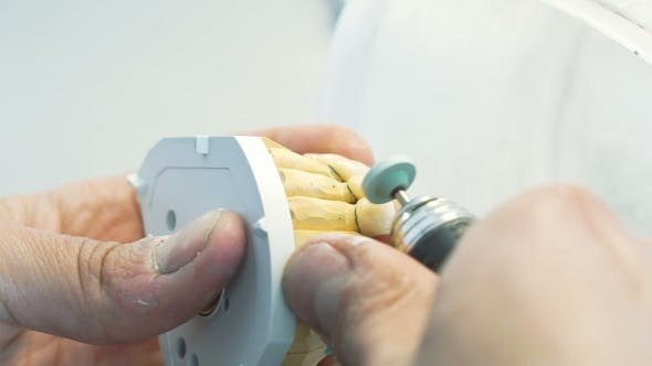 of Grinding Teeth Crowns with Instruments in Dental Lab