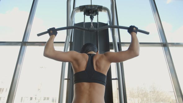 Cover Image for Young Brunette Woman Flexing Back And Hand Muscles On Gym Machine