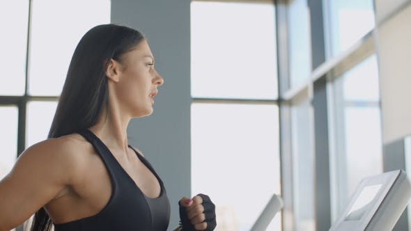 Cover Image for Young Woman Running On A Treadmill Cardio Training Gym