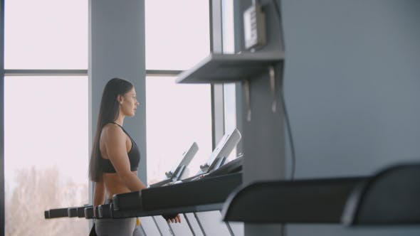 Cover Image for Young Woman Walking On A Treadmill In The Gym Cardio