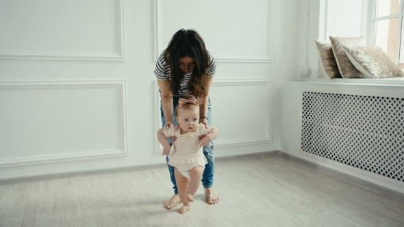 Thumbnail for Baby Girl Doing His First Steps with Mother Help