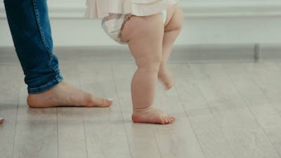 Legs of Mother and Baby. The Baby's First Steps