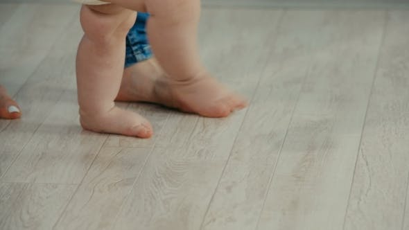 Thumbnail for Legs of Mother and Baby. Baby Daughter Take First Steps