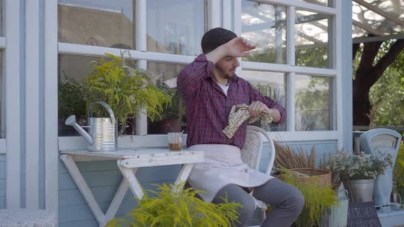 Thumbnail for Tired Young Professional Farmer Taking Off Garden Gloves and Drinking the Tea Sitting at the Village