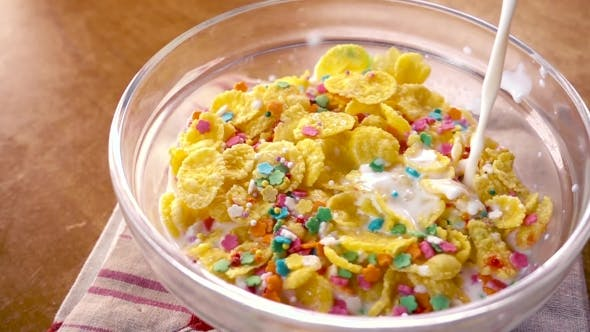 Crispy Yellow Corn Flakes Into the Bowl for the Morning a Delicious Breakfast with Milk.