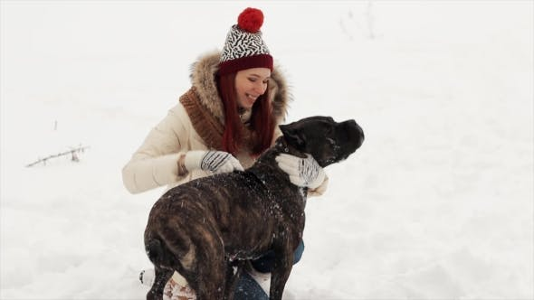 Thumbnail for Happy Girl Playing with a Dog in Winter