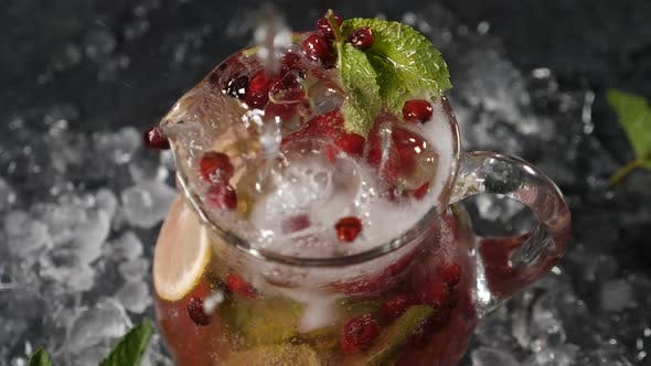 Aerated Cold Water Being Poured in Transparet Jar with Sliced Lime Berries and Ice Cubes