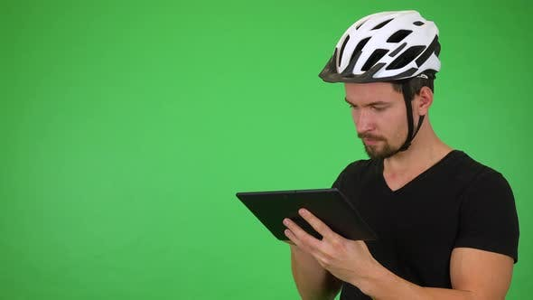 Thumbnail for A Young Handsome Cyclist Works on a Tablet, Then Smiles at the Camera - Green Screen Studio