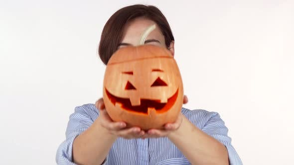 Thumbnail for Woman Hiding Her Face Behind Carved Halloween Pumpkin