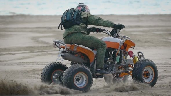 Thumbnail for A Man Wearing a Helmet on His Head Performs an Extreme Trick on a Sports ATV on the Beach Area