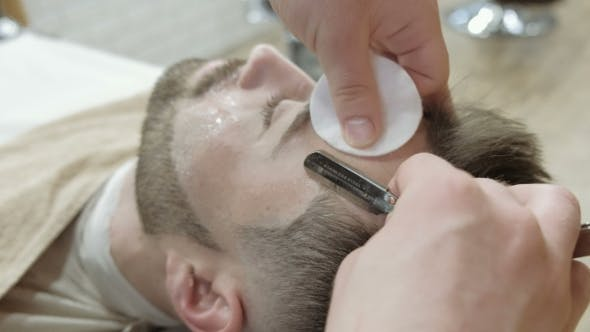 Thumbnail for Portrait of Handsome Young Man Getting Beard Shaving with Straight Razor. Focus on the Blade