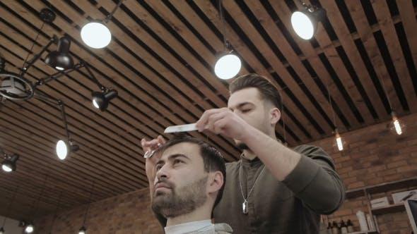 Meister schneidet Haare und Bart der Männer im Friseur, Friseur macht Frisur für einen jungen Mann