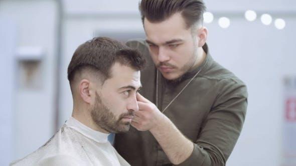 Thumbnail for Meister schneidet Haare und Bart der Männer im Friseur, Friseur macht Frisur für einen jungen Mann