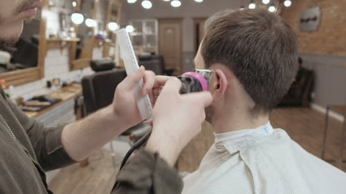 Professional Hairdresser Doing Haircut Men's Hair. Cutting Electric Razor. Beauty Saloon. Male