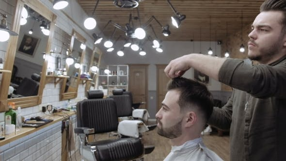 Thumbnail for Handsome Bearded Man Is Smiling While Having His Hair Cut By Hairdresser at the Barbershop