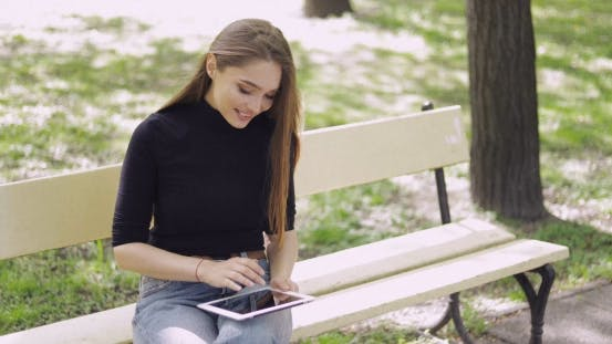 Thumbnail for Cheerful Young Woman Using Tablet Outside