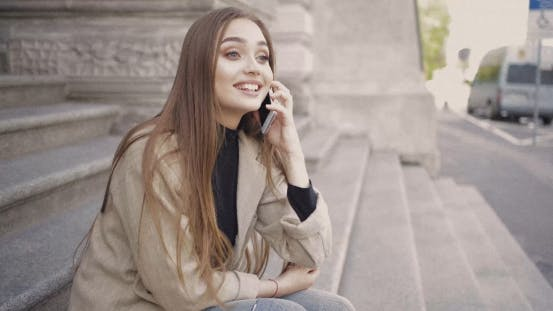 Thumbnail for Cheerful Girl Talking Phone Outside