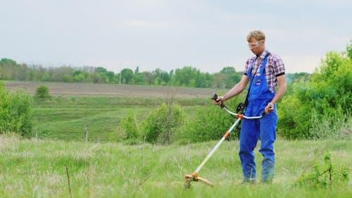 Worker Mows Green Grass Manual Lawnmower
