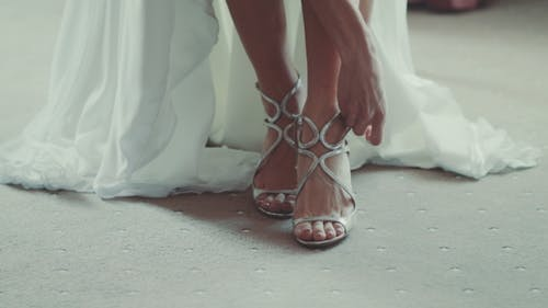 Bride Putting On Shoes For Wedding Day
