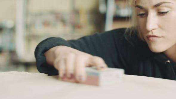 Thumbnail for Female Carpenter Polishing Wood In Workshop