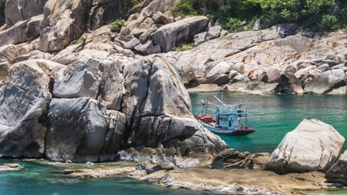 Fisher Boat Moving on Waves at Anchor Between Huge Stone Blocks in Tanote Bay, Koh Tao Island