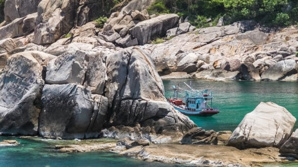Thumbnail for Fisher Boat Moving on Waves at Anchor Between Huge Stone Blocks in Tanote Bay, Koh Tao Island