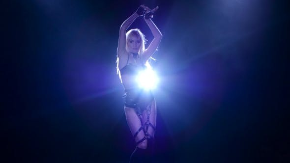 Thumbnail for Go-Go Girl Dancing in Leather Underwear Illuminated By White Spotlight