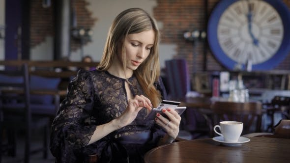 Thumbnail for Lady Buying Online with a Credit Card and Smartphone Sitting in Restaurant with People in the