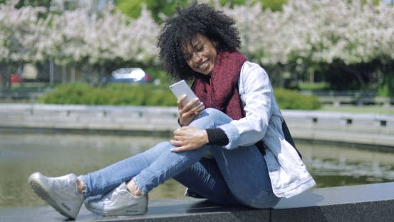 Thumbnail for Cheerful Woman with Smartphone Outside