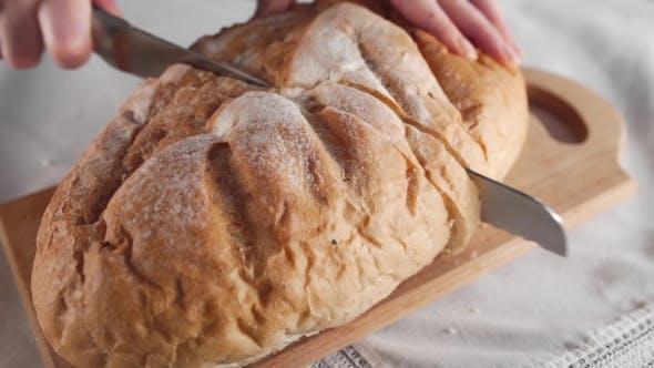 Thumbnail for Hausfrau schneidet Brot durch lange Messer auf dem Holzbrett Familie Abendessen Laib Brot Bäckerei