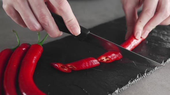 Thumbnail for The Cook Slices Hot Chili Peppers on the Board, Spicy Food, Meals with Vegetables, Vegetarian Food