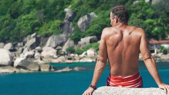 Thumbnail for Tanned Travler Men Relax on Stone in Front of Tanote Bay on Koh Tao Island, Thailand, Asia