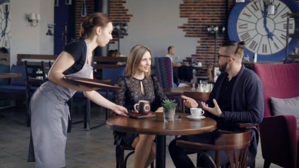 Thumbnail for Waiter Delivering Order. Female Waiter Delivering Order for Young Couple Sitting in Cafe.