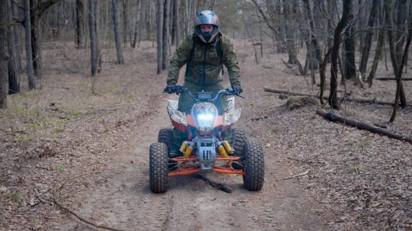 Thumbnail for Man in Protective Equipment and Helmet Operating ATV Moving Along the Road in the Forest Gliding