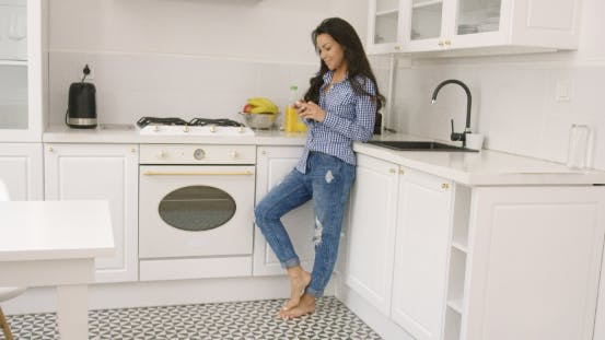 Thumbnail for Fit Young Female Using Phone in Kitchen