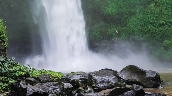 Thumbnail for of Nungnung Waterfall, Falling Water Hitting Water Surface, Some Huge Wet Rocks in Front of Frame