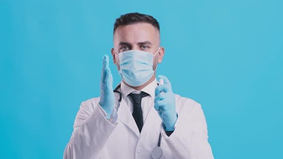 Thumbnail for Coronavirus Prevention, Doctor in Medical Mask and Gloves Disinfecting Hands with Spray Sanitizer