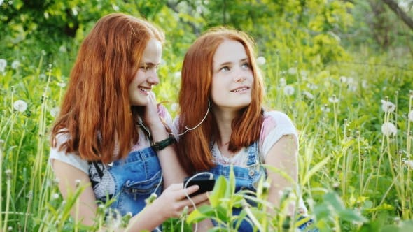 Thumbnail for Two Cute Twin Sisters Relax on the Nature, Use a Smartphone, Listen To Music on Headphones