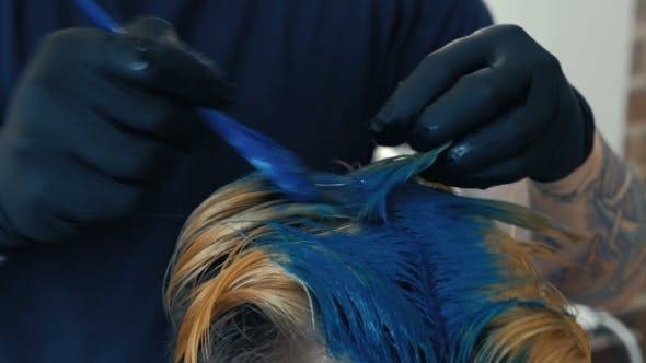 Professional Hairdresser Dyeing Hair of Her Client. Blue Hair Color.
