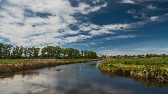 River in Spring on a Bright Sunny Day. Blue Sky with White Clouds