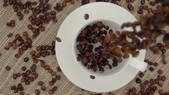 Des grains de café entiers tombent dans la tasse.